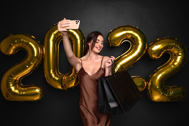 Mulher morena com vestido elegante segurar sacolas de compras, fazendo fotos de selfie em smartphone em backgro preto.