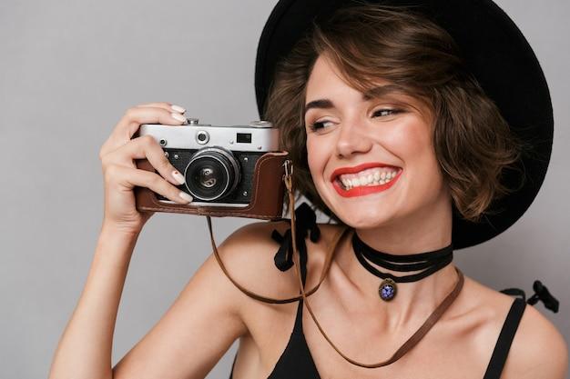 Mulher morena com vestido preto e chapéu fotografando na câmera retro, isolada sobre a parede cinza