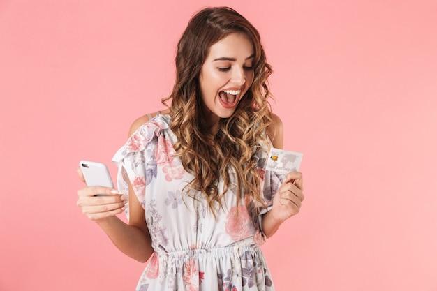Mulher morena com vestido segurando smartphone e cartão de crédito, isolado em rosa