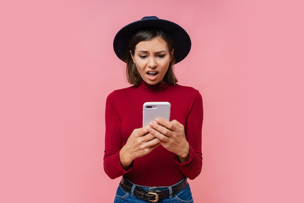 Mulher morena confusa segurando um celular moderno, digitando mensagens no dispositivo smartphone, isolado