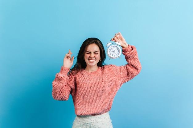 Mulher morena cruzou os dedos e segura o despertador branco. modelo de suéter grande posando na parede azul.