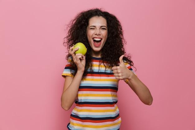 Mulher morena de 20 anos com cabelo encaracolado sorrindo e segurando uma maçã verde isolada na rosa
