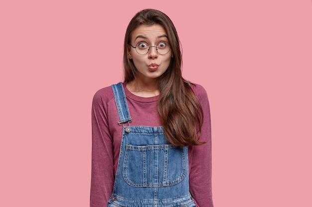 Mulher morena de aparência agradável faz beicinho, faz careta, usa macacão roxo e macacão jeans