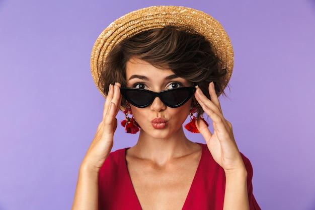 Mulher morena de beleza no vestido, chapéu de palha e óculos de sol