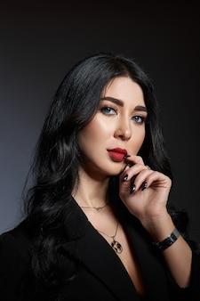 Mulher morena de beleza sexy em poses de jaqueta preta no estúdio. menina elegante com bela maquiagem natural