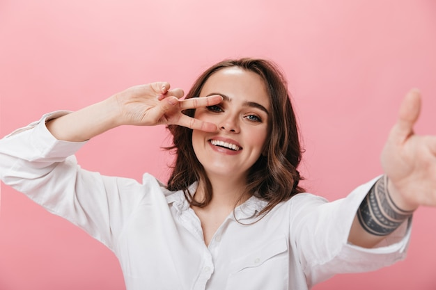 Mulher morena de bom humor leva selfie isolada. menina encaracolada na camisa branca sorri amplamente e mostra o símbolo da paz no fundo rosa.