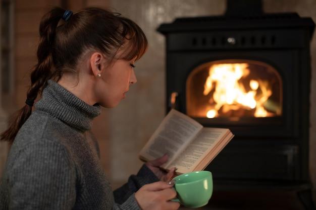 Mulher morena de cabelo muito comprido com rabo de cavalo em um suéter cinza lendo perto da lareira com uma xícara na mão em um aconchegante quarto escuro
