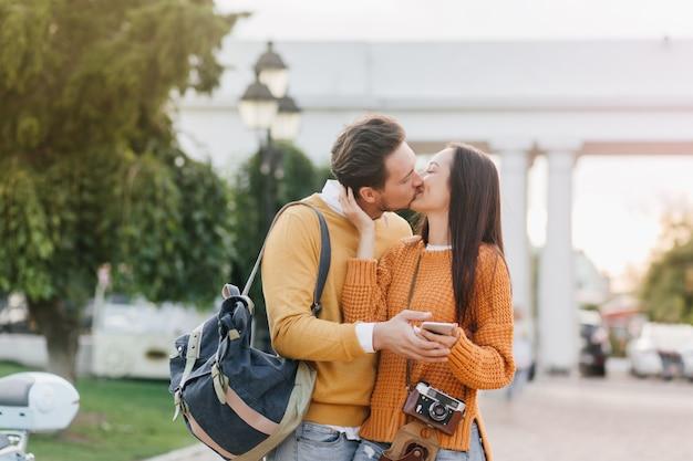 Mulher morena de cabelos compridos com uma câmera beijando o namorado na cidade borrada