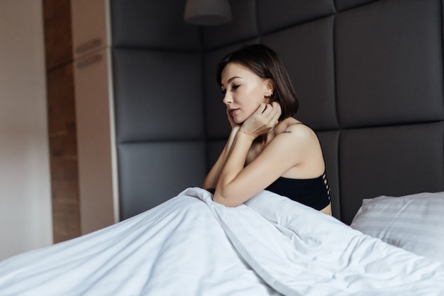 Mulher morena de cabelos muito longos na cama branca na luz suave da manhã sob o edredom