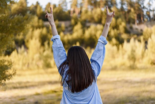 Mulher morena de camisa azul com as mãos para cima mostra dois