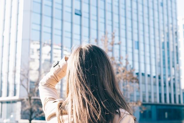 Mulher morena de casaco bege olha para o prédio