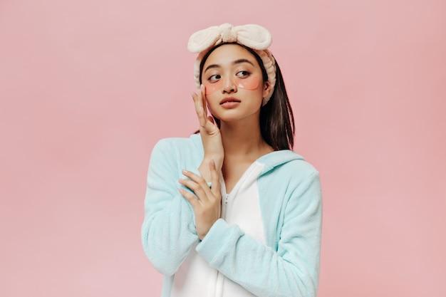 Mulher morena de olhos castanhos em pijama azul e tiara macia tocando suavemente o rosto e posa com tapa-olhos cosméticos na parede rosa