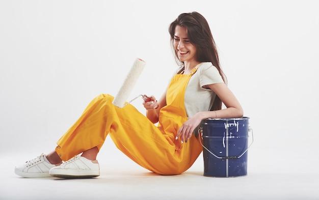 Mulher morena de uniforme amarelo sentada contra uma parede branca no estúdio