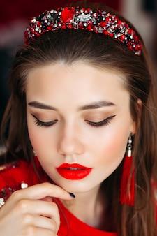 Mulher morena de vermelho com profissional maquiagem tocando o rosto.