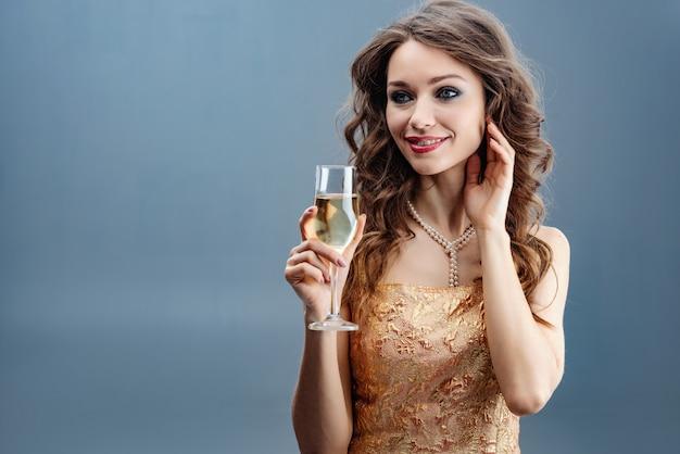 Mulher morena de vestido dourado e colar de pérolas com taça de champanhe e tocar-se rosto para a mão