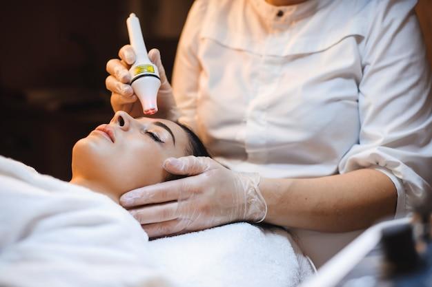 Mulher morena deitada fazendo procedimentos de tratamento facial em salão de spa usando aparelhos modernos