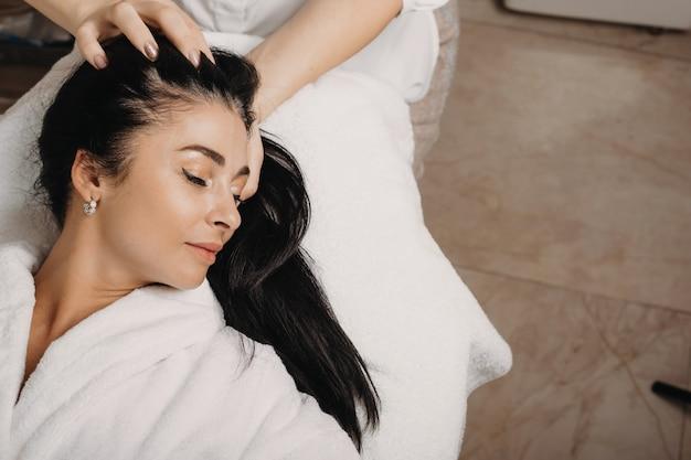 Mulher morena deitada no sofá com os olhos fechados durante uma massagem na cabeça no salão