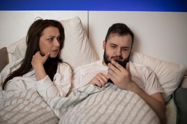 Mulher morena descontente, com ciúme, observa seu namorado barbudo conversando com alguém em seu smartphone