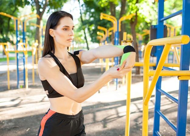 Mulher morena deslumbrante e flexível, usando roupa esportiva preta, esticando o braço