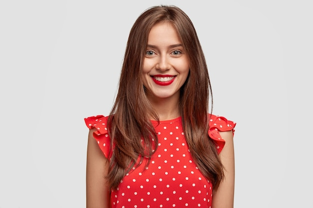 Mulher morena divertida com cabelo escuro, usa batom vermelho, vestida com um vestido da moda de bolinhas