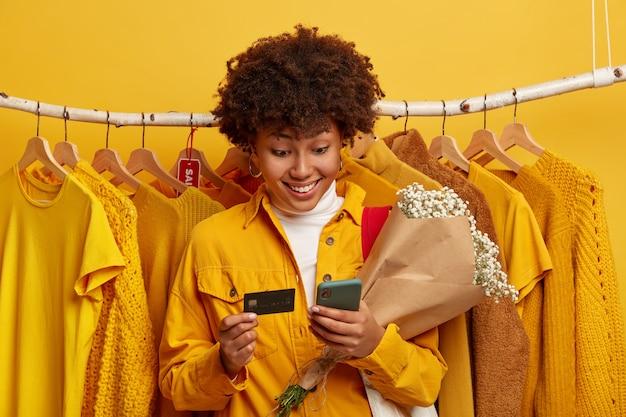 Mulher morena e cacheada usa cartão de crédito e telefone celular moderno