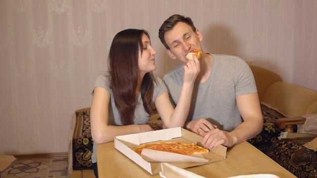 Mulher morena e homem comendo pizza em casa.
