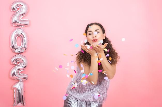 Mulher morena elegante alegre com cabelos cacheados em roupas festivas joga confetes em uma parede rosa com balões prateados à esquerda para o conceito de ano novo