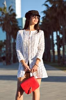Mulher morena elegante caminhando, roupa de estilo luxuoso chique, edifícios modernos e palmas, cores enfraquecidas.