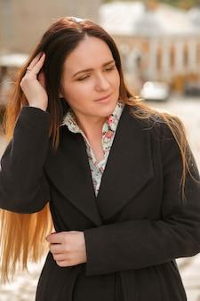 Mulher morena elegante com cabelo comprido, vestindo um casaco azul da moda e uma camisa de algodão posando em um dia ensolarado