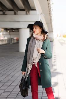 Mulher morena elegante com casaco verde e chapéu preto, posando para a cidade