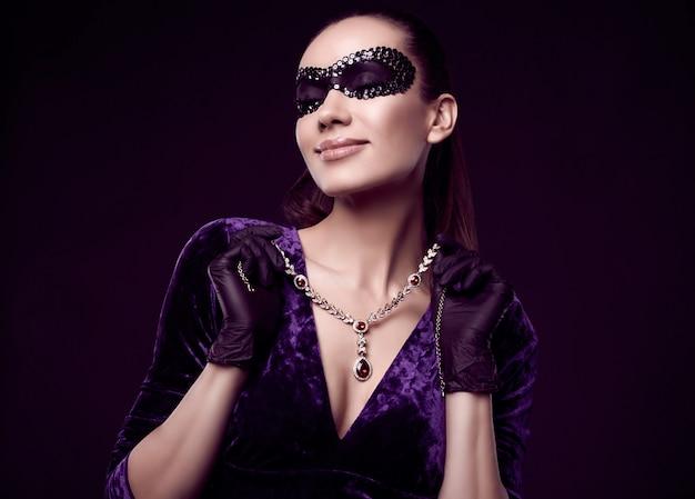 Mulher morena elegante com lindo vestido roxo, máscara de lantejoulas e luvas pretas