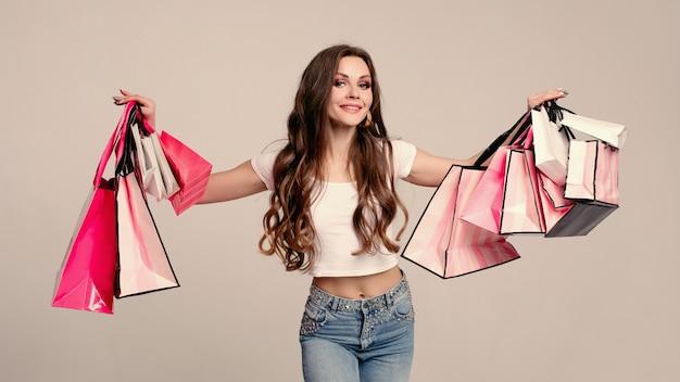 Mulher morena elegante com um monte de sacolas de compras
