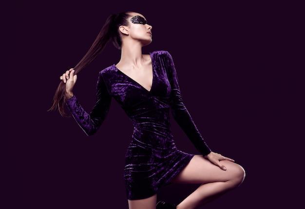 Mulher morena elegante e charmosa com lindo vestido roxo e máscara de lantejoulas