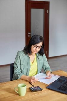 Mulher morena elegante em copos, sentado à mesa de madeira com o bloco de notas, trabalhando em seu escritório, moderno local de trabalho, freelancer, trabalhando em casa.