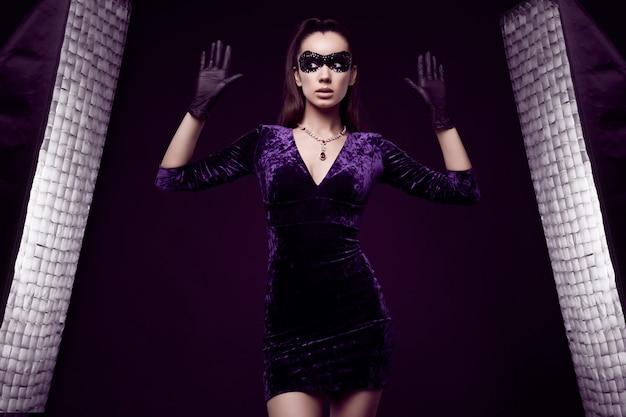 Mulher morena elegante em lindo vestido, máscara de lantejoulas e luvas se rendendo