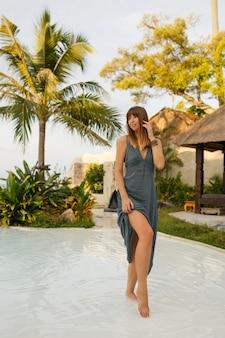 Mulher morena elegante em um vestido sexy, posando em um restaurante de praia elegante em estilo asiático. toda a extensão.