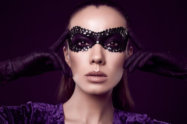 Mulher morena elegante encantadora com máscara de lantejoulas e luvas