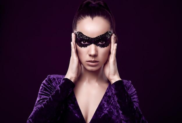 Mulher morena elegante encantadora com vestido roxo e máscara de lantejoulas