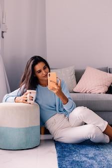 Mulher morena em forma de blogueira de moda europeia sentada no chão da sala perto do sofá