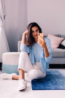 Mulher morena em forma de blogueira de moda europeia sentada no chão na sala de estar perto do sofá com o telefone