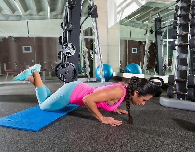 Mulher morena em joelhos de ginásio push-up push-up