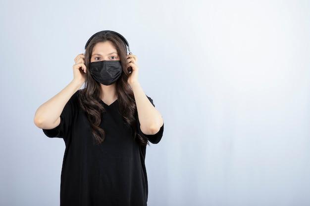 Mulher morena em máscara médica, ouvindo música em fones de ouvido.