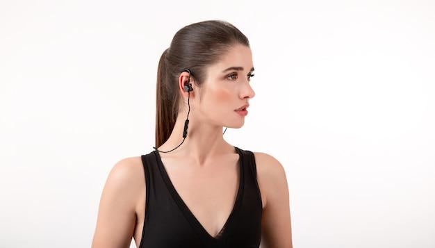 Mulher morena em top preto para correr ouvindo música em fones de ouvido posando em cinza