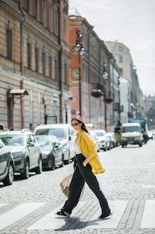 Mulher morena em uma jaqueta amarela e calça preta, óculos escuros e saco de corda andar na rua.