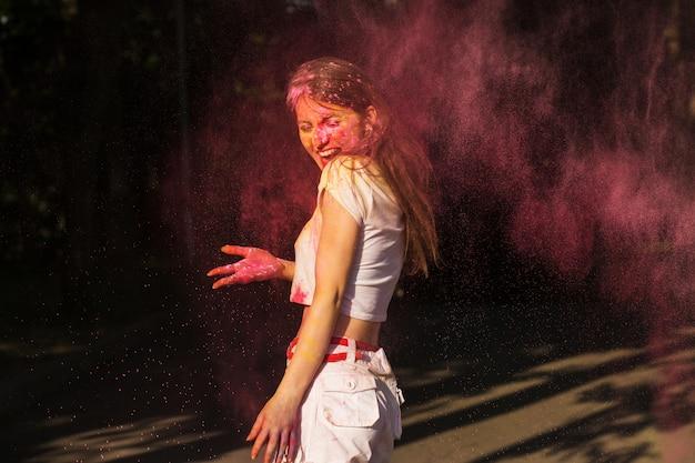 Mulher morena emocional brincando com a tinta rosa seca holi explodindo ao seu redor