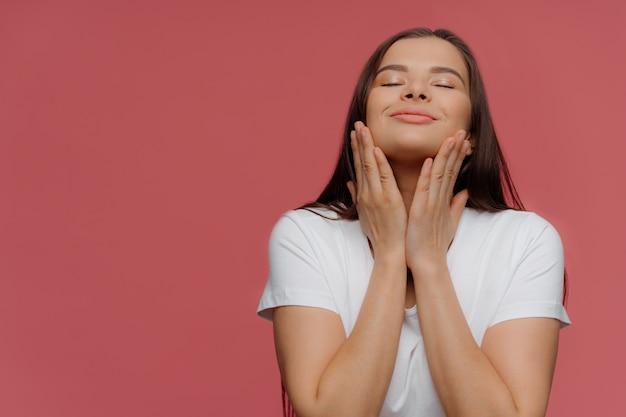 Mulher morena encantada goza de suavidade da pele após procedimentos de spa