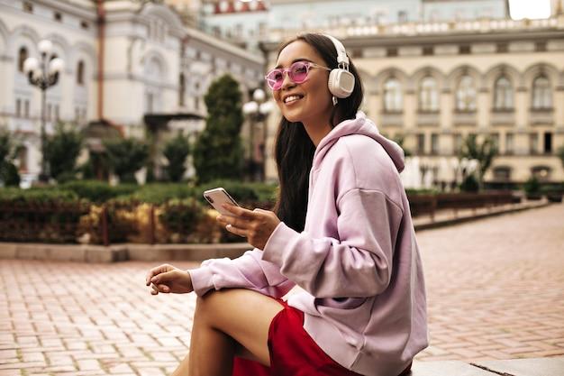 Mulher morena encantadora com capuz rosa e óculos escuros desvia o olhar, segura o telefone e ouve música com fones de ouvido do lado de fora