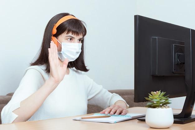 Mulher morena encantadora com fones de ouvido laranja e uma máscara protetora médica com uma videochamada e um gesto de boas-vindas, sentada em uma mesa em casa na frente de um monitor de computador