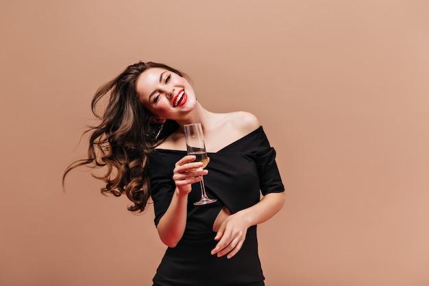 Mulher morena encantadora com lábios vermelhos é linda, sorrindo e brincando com o cabelo. menina com roupa preta, posando com taça de champanhe.