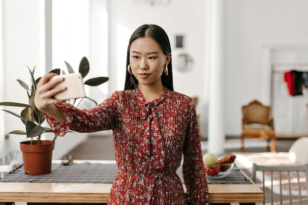 Mulher morena encantadora com vestido floral vermelho tirando selfie na cozinha